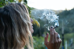 woman smoking a joint looking out over the landscape
