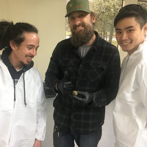 3 cannassuers posing with a nug of weed