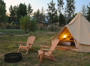 a glamping site with canvas tent and 2 Adirondack chairs by a fire pit
