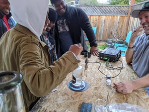 People laughing at an outdoor dab bar in The Emerald Triangle