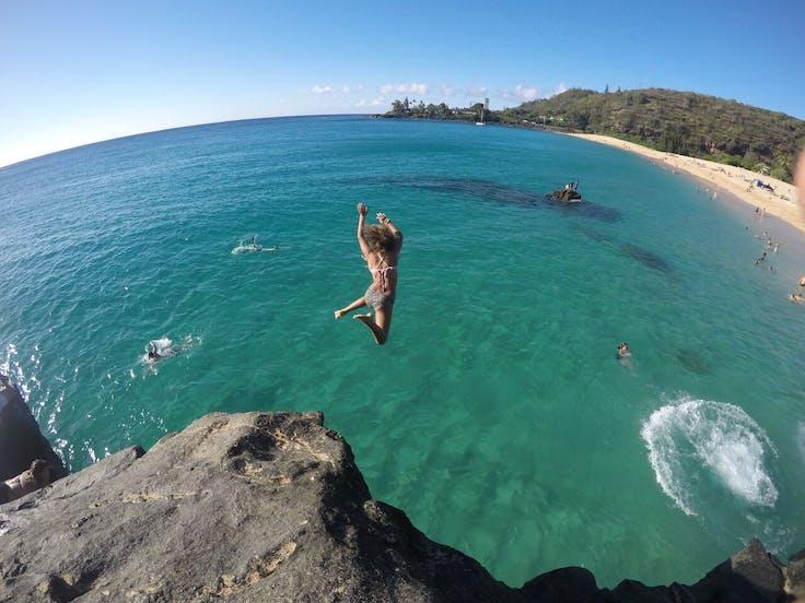 Girl jumping off rock at Waimea Bay