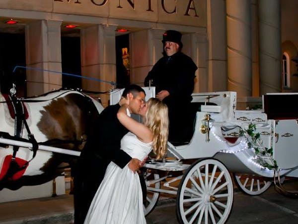 couple kissing in front of wedding carriage