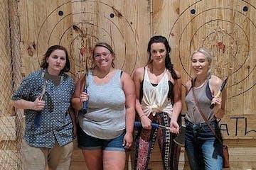 women standing before wooden axe throwing targets
