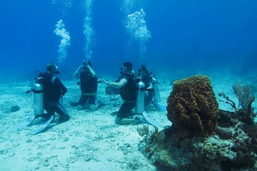 group of scuba divers sitting on sea floor in a circle