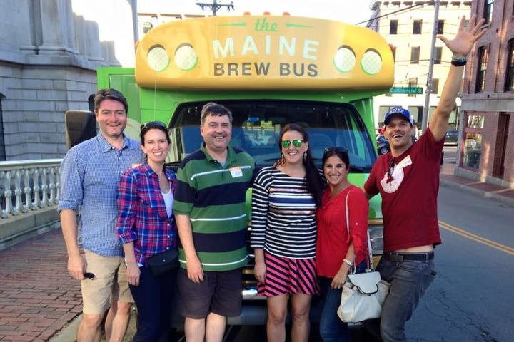 A group of brewery tour participants posing outside their tour bus in Portland, Maine