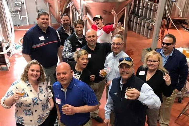 A group of tour participants pose for a photo at a Maine brewery