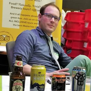 a man sitting at a table with a bottle of beer