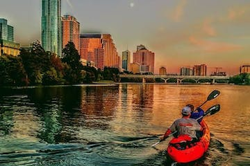 people kayaking in city lake during sunset