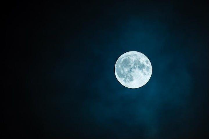dark photo of the full moon in the night sky