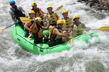 people white water rafting down strong rapids