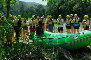 group of people in a jungle standing by raft