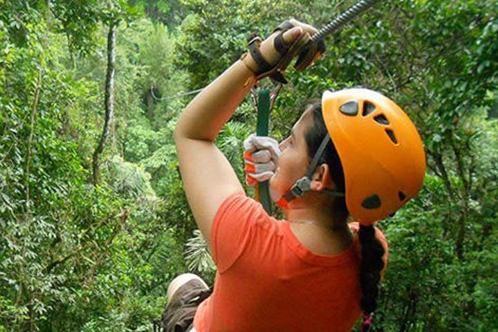 woman ziplining through tropical forest canopy