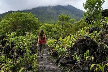 woman from behind walking in jungle landscape of costa rica