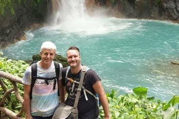 two men posing before a waterfall in a tropical forest in costa rica