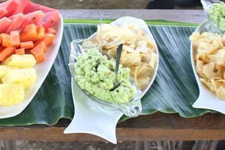 chips and guacamole and fruit on a plate