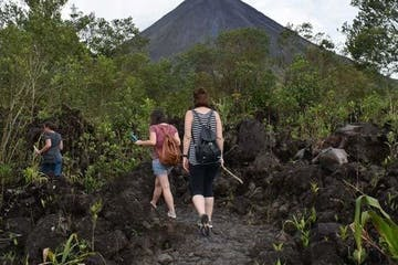 people walking in jungle landscape with volcano in distance