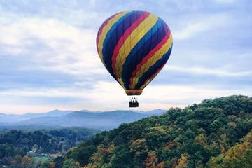 Hot air balloon flying over mountains