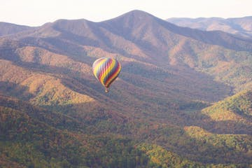 Hot air balloon flying over mountains in the fall