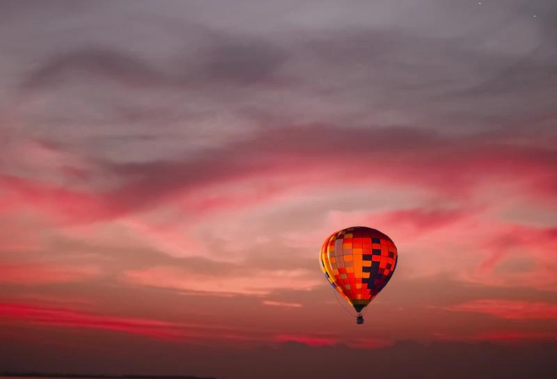 a hot air balloon ascends at sunset