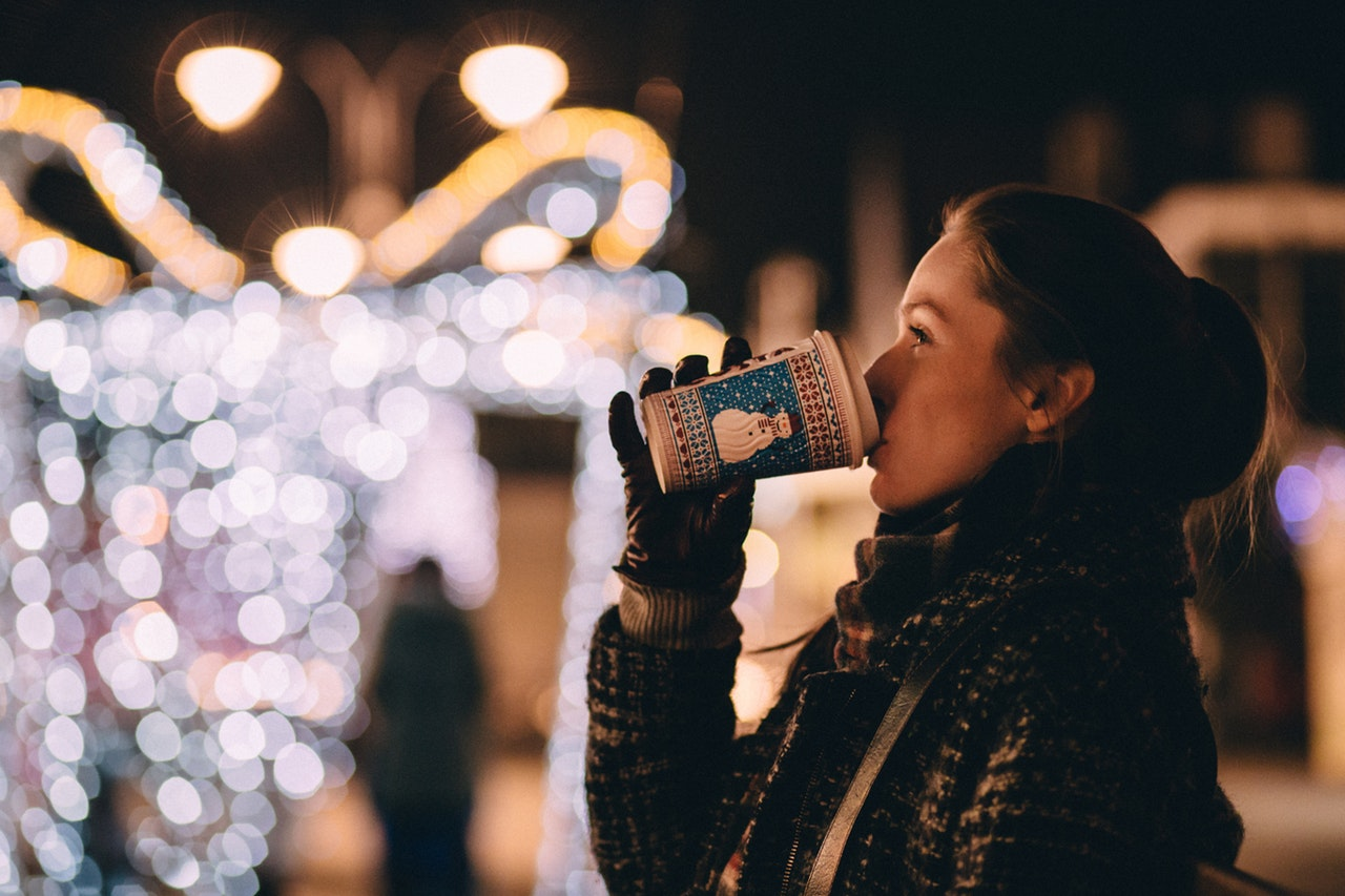 A woman drinking a festive drink in front of christmas lights