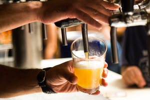 A bar tender pouring a beer from a tap