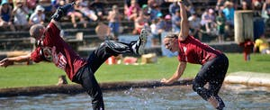 Man falling off a log in a competition