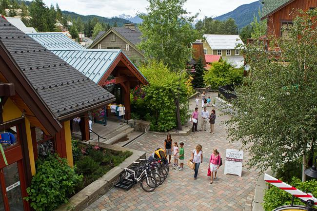 Whistler Creekside Village shops with shoppers and children.
