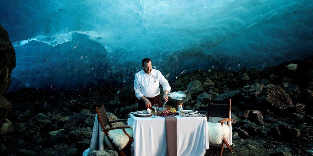 Chef setting a table in a glacier