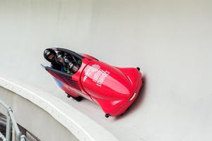 Two people at the sliding centre in a bobsled