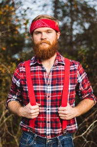 Lumberjack with suspenders, and beard, looking into the camera