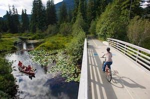 Kid biking over bridge and canoe