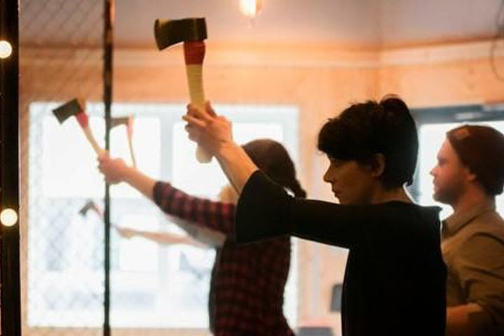 Two people getting ready to throw axes