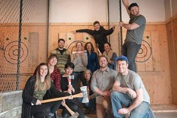 A group of friends posing in front a axe throwing targets