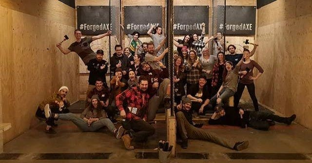 A group of people posing for a picture during the axe throwing league