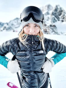 A woman skiing, looking into the camera