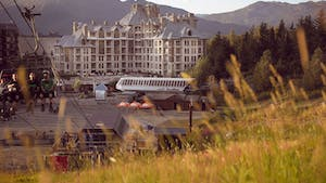 A hotel in Whistler at the base of the mountain, looking through the grass.