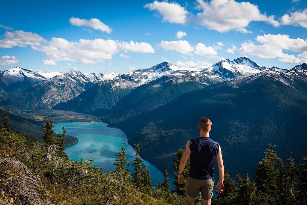 Man standing on mountain overlooking lake in Whistler