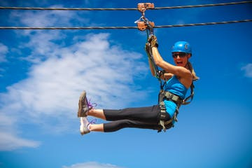 A woman soaring past a cloud as she ziplines