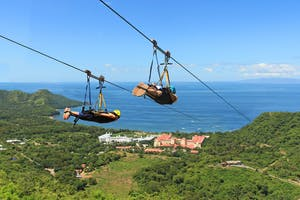two people superman zip line with forest and ocean view