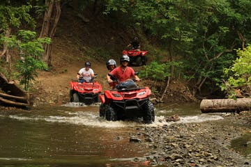 A group riding ATVs through the jungle