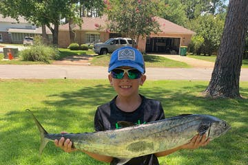 boy on lawn with fish