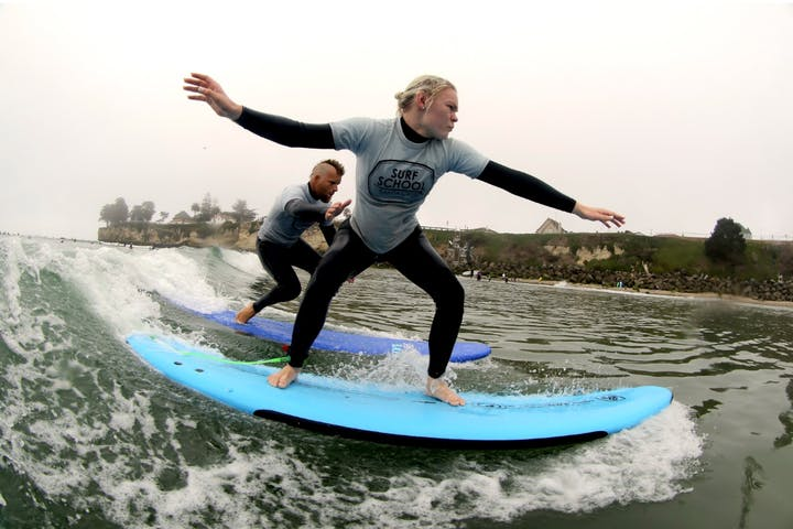 A surfing instructor teaching someone how to surf in Santa Cruz, CA
