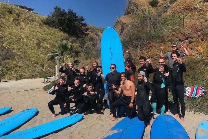 A group of surfers posing on a beach in Santa Cruz, CA