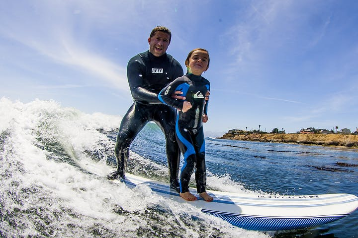 Bud Freitas instructing a young child how to surf in Santa Cruz, CA