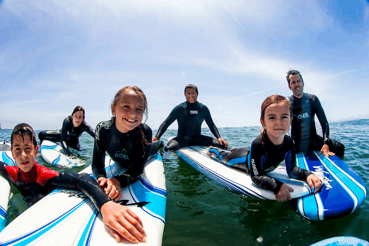 A group of young children posing on their surf boards during a surf lesson in Santa Cruz, CA