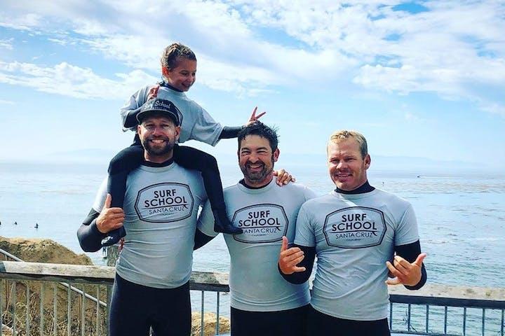 A group of surfers posting by the ocean in Santa Cruz, CA