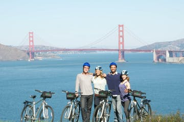 a man with a bicycle in front of the golden gate bridge with his tour group