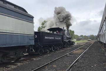 a train on a track with smoke coming out of it