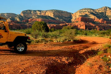 yellow jeep parked in the red rocks of sedona arizona
