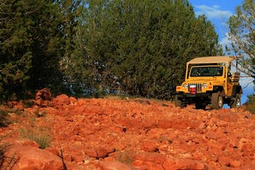 yellow jeep on the red rocks of sedona with forest in the background